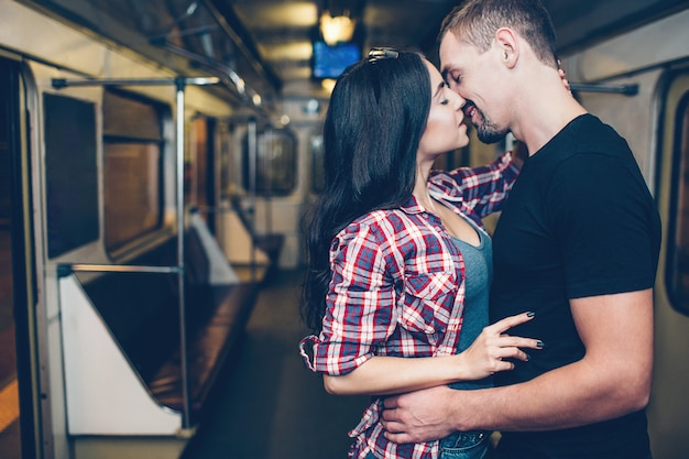 Young man and woman use underground. couple in subway. romantic kiss.