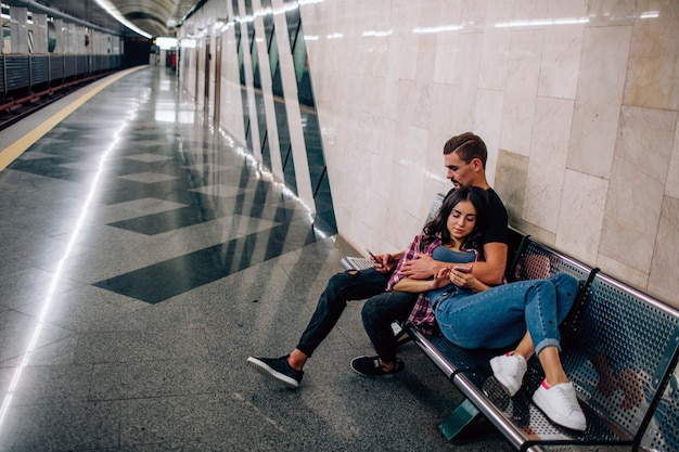 Young man and woman use underground. couple in subway. sitting and lying on bench. empty metro station. love story. romance. love at first sight.