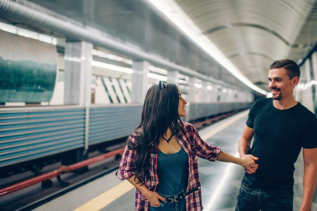 Young man and woman use underground. couple in subway. young man follow woman and hold her hand. they look at each other and smile. love story.