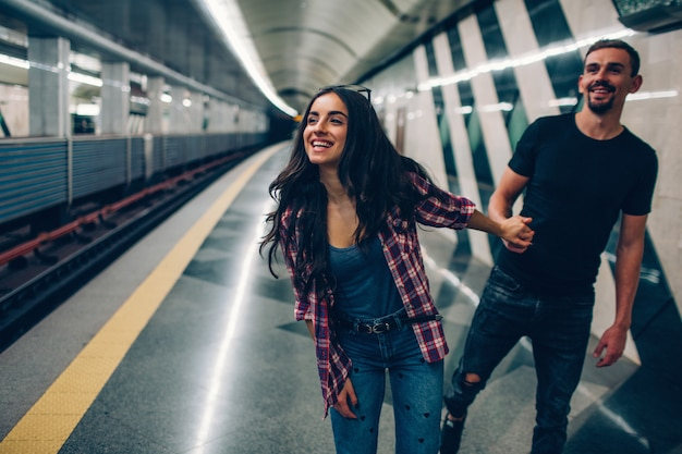 Young man and woman use underground. couple in subway. young woman hold man in hand. he follow her. young woman smiles. fast train moves. action. love story.