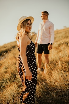 Young man and woman walking in the meadow at sunset in summer near the lake.