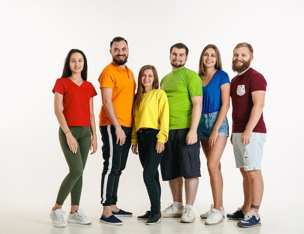 Young man and woman weared in lgbt flag colors on white wall. caucasian models in bright shirts. look happy, smiling and hugging. lgbt pride, human rights and choice concept.