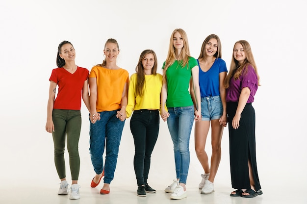 Young man and woman weared in lgbt flag colors on white wall. caucasian models in bright shirts. look happy together, smiling and hugging. lgbt pride, human rights and choice concept.