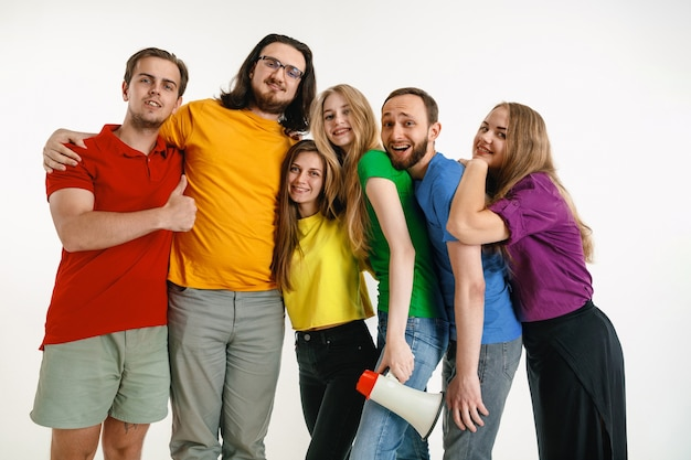 Young man and woman weared in lgbt flag colors on white wall. caucasian models in bright shirts.