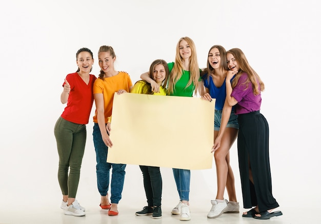 Young man and woman weared in lgbt flag colors on white wall. models in bright shirts