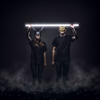 Young man and woman wearing black clothes and masks of a rabbit and cat with a light over them