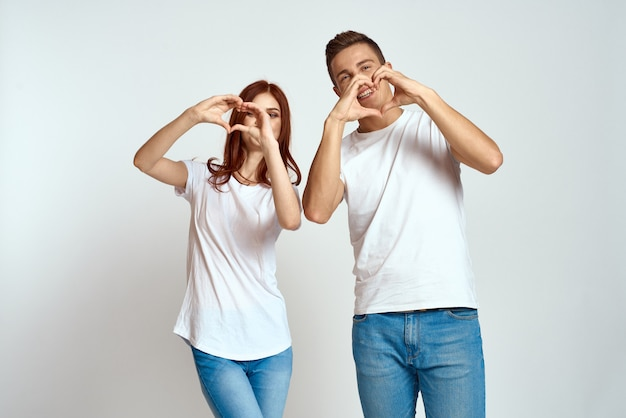 Young man and woman in white t-shirts on a light