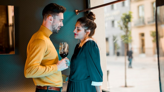 Young man and woman with glasses of wine near window