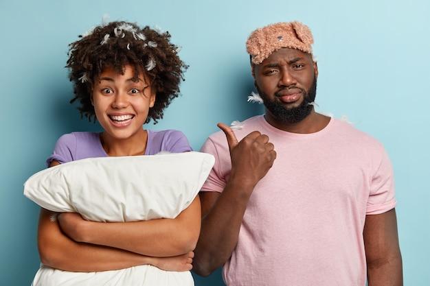 Giovane uomo e donna con maschera per dormire e cuscino