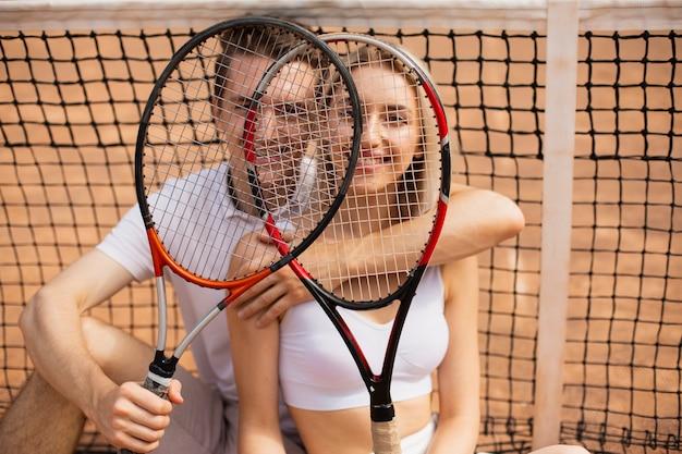 Молодой мужчина и женщина с теннисными ракетками