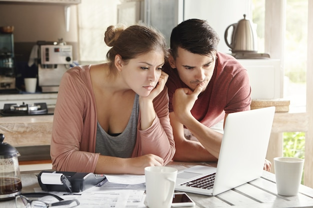 Young man and woman working together on laptop, paying utility bills via internet or using online mortgage calculator to save money on home loan, looking at screen with serious concentrated expression