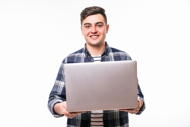Young man work with laptop computer in front of white studio wall