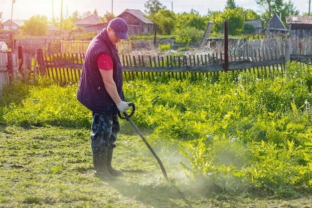 若い男は庭の草を刈るストリングトリマーで動作します