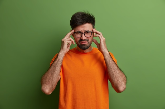 Young man worker has unbearable headache, keeps hands on temples, frowns face from pain, feels painful migraine, overworked during preparing project, wears transparent glasses and orange t shirt