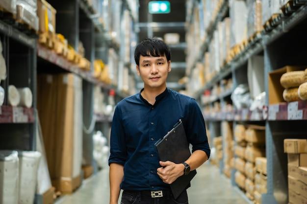 Молодой человек рабочий держит буфер обмена и проверяет инвентарь в складском магазине