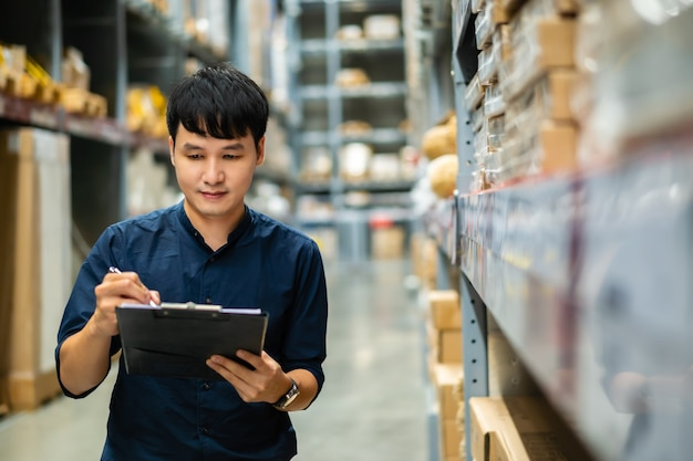 Young man worker holding clipboard and checking inventory in the warehouse store