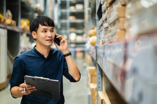 젊은 남자 작업자가 휴대 전화로 이야기하고 클립 보드를 들고 창고 상점에서 재고를 확인합니다.
