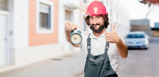 Young man worker with an alarm clock