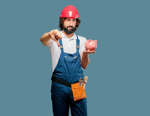 Young man worker with a piggy bank