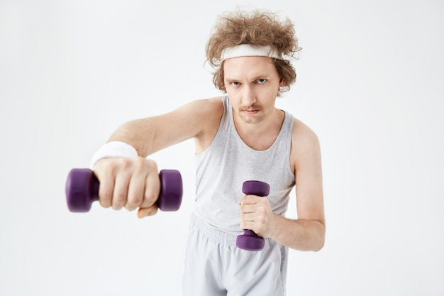 Young man working on arm muscles training with dumbbells