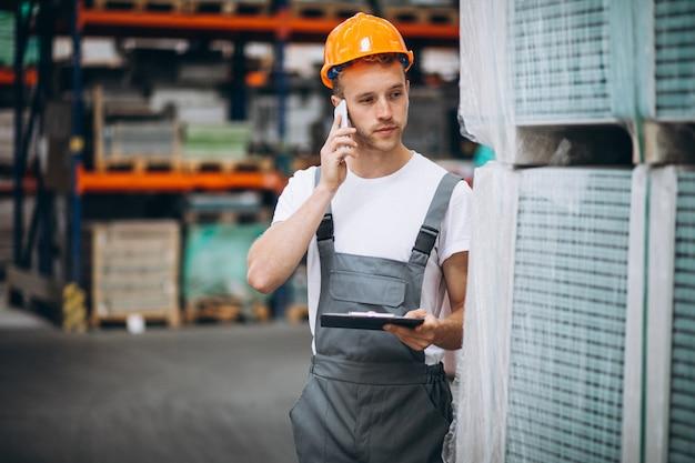 Молодой человек работает на складе с ящиками