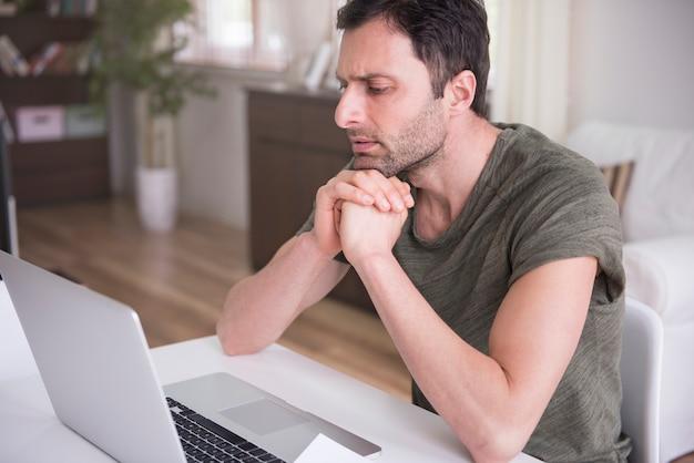 그의 노트북으로 집에서 일하는 젊은 남자