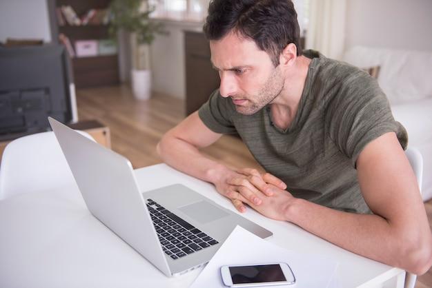 彼のラップトップで自宅で働く若い男