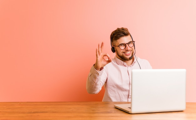 Young man working in a call center cheerful and confident showing ok gesture