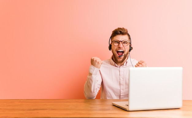 Young man working in a call center cheering carefree and excited. victory concept.