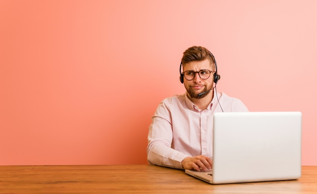 Young man working in a call center confused, feels doubtful and unsure