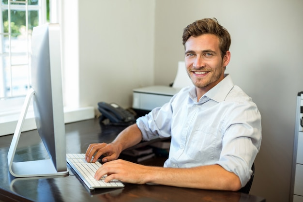 Young man working on computer at desk in office