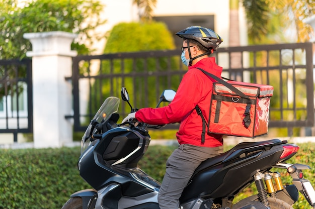 Young man working for a food delivery service checking with road motorcycle in the city