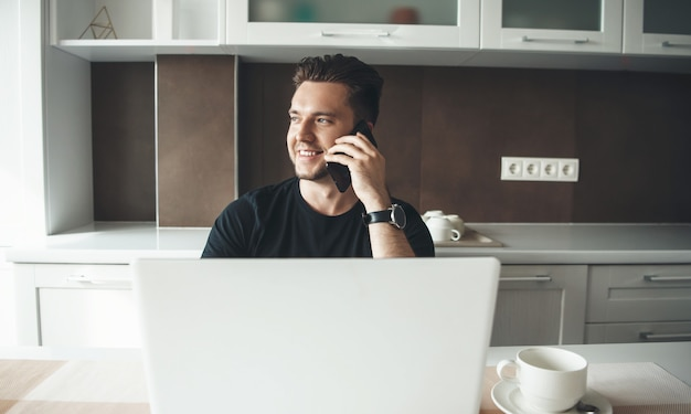 모바일 및 미소에 얘기하는 노트북과 부엌에서 집에서 일하는 젊은 남자