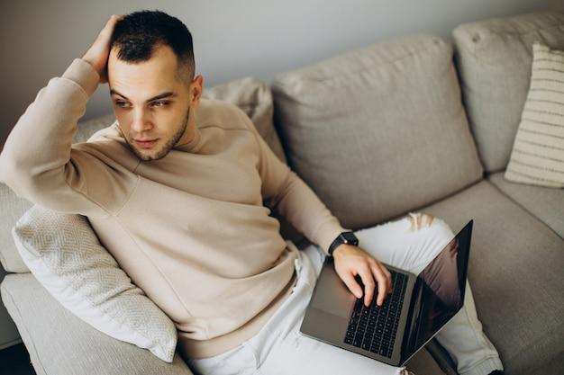 Молодой человек, работающий дома на ноутбуке