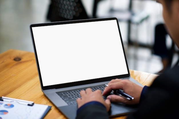 Young man working on his laptop with blank copy space screen for display advertise.