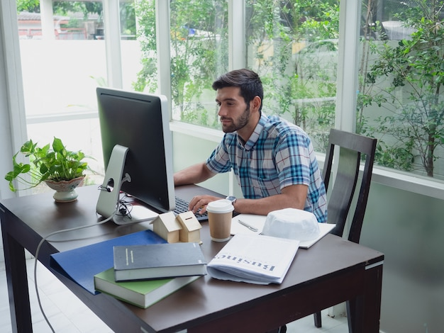 Young man working at home with coffee and newspaper