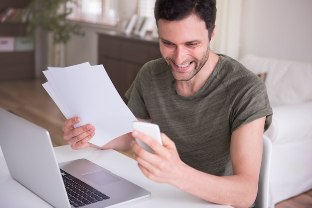 Giovane che lavora a casa con il suo laptop