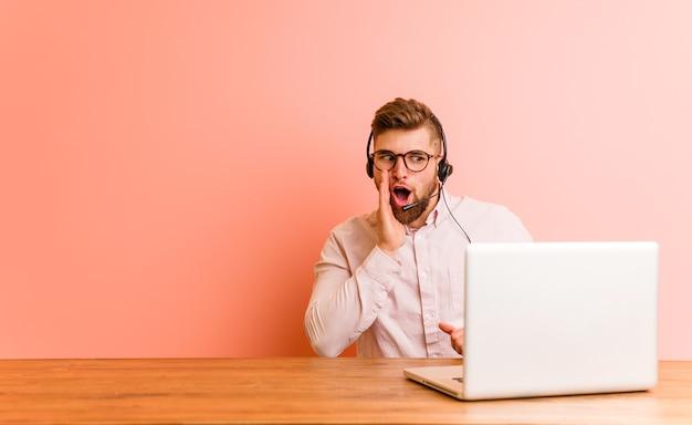 コールセンターで働く若い男が秘密のホットブレーキングニュースを言ってよそ見