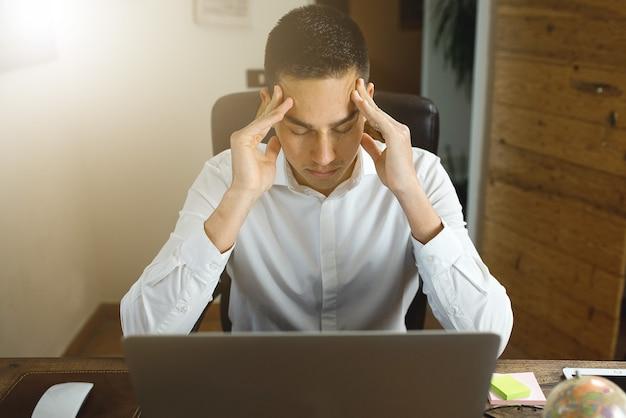 컴퓨터 책상에 사무실에서 일하는 젊은 남자. 눈을 감고 머리를 손에 든다. 스트레스, 과로 개념.