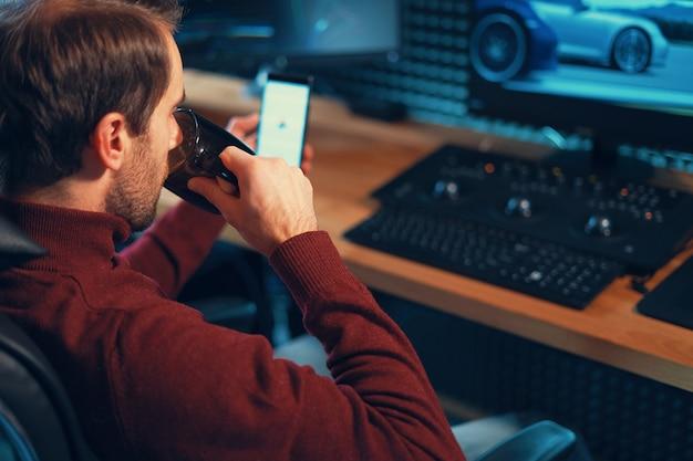 Молодой человек, работающий в студии с помощью смартфона и компьютера.