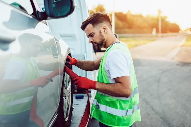 Молодой человек работает в службе буксировки на дороге. концепция помощи на дороге.