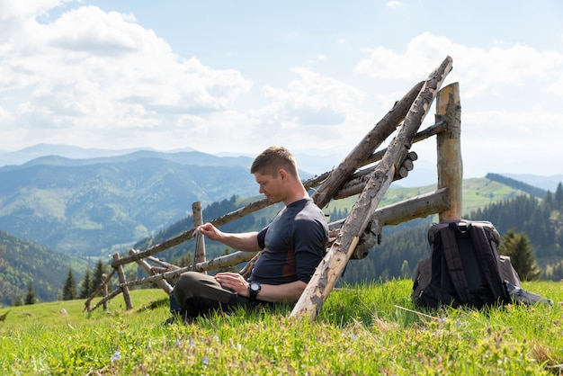 Young man working on a laptop beech outdoors nature remote work