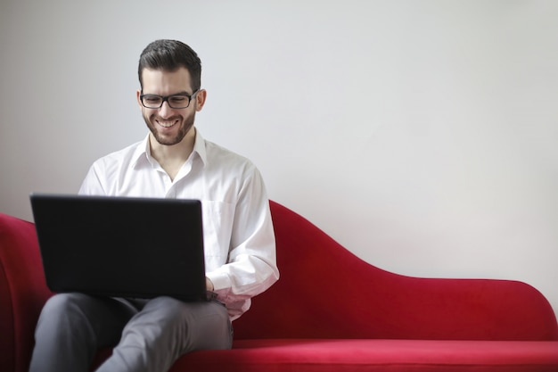Young man working on a laptop on a sofa