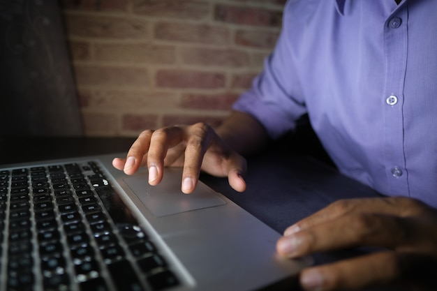 Young man working on laptop stealing personal data