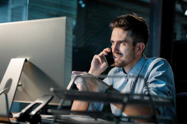 Молодой человек работает поздно в офисе