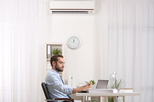 Young man working in office with air conditioner
