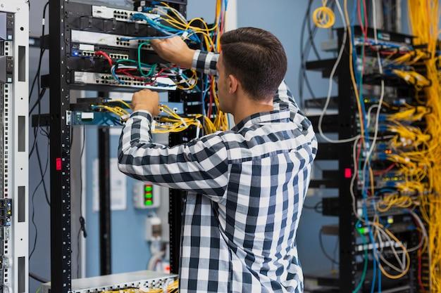 Молодой человек, работающий на ethernet коммутатора среднего снимка