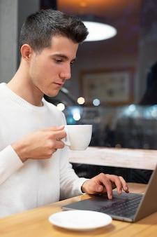 コーヒーショップ、コンピューターに入力する若い学生で彼のラップトップに取り組んでいる若い男。