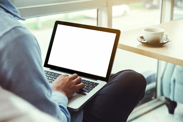 Молодой человек, работающий на своем ноутбуке в кафе