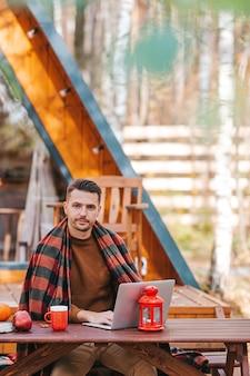 秋の日に屋外でノートパソコンに取り組んで、木製のテーブルに座ってコーヒーを飲む若い男